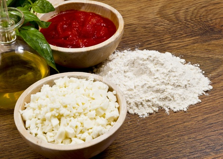 tomato, oil and another ingredients for pizza in wooden table