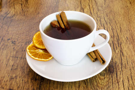 Cup of orange tea with cinnamon on wooden table