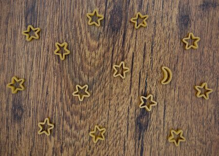 pasta stars and moon on wooden table Stock Photo - 17352069