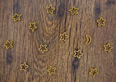 pasta stars and moon on wooden table Stock Photo - 17352069