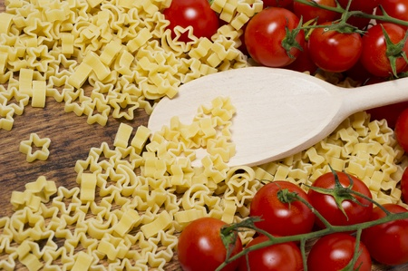 italian pasta and little tomatoes on wooden table Stock Photo - 17352133