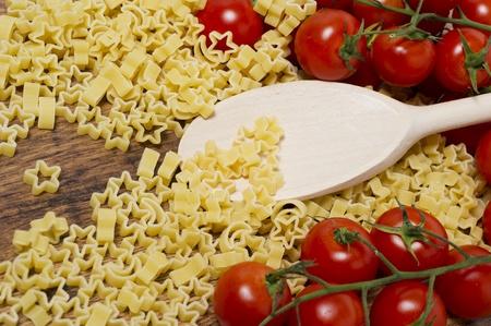italian pasta and little tomatoes on wooden table Stock Photo - 17352133