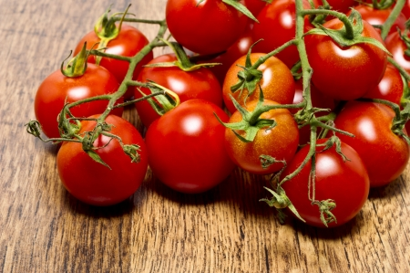 Tomatoes in trusses on wooden table Stock Photo