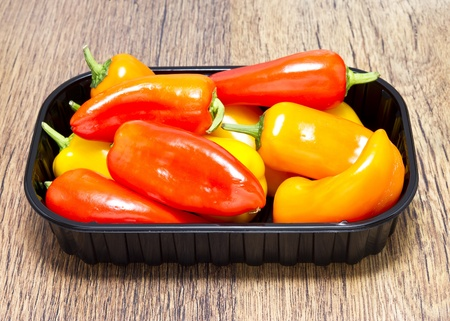 Mixed Peppers in plastic basket on wooden table Stock Photo