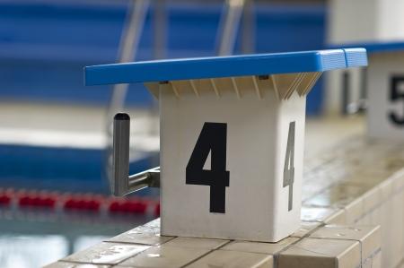 white and blue swimming pool starting block