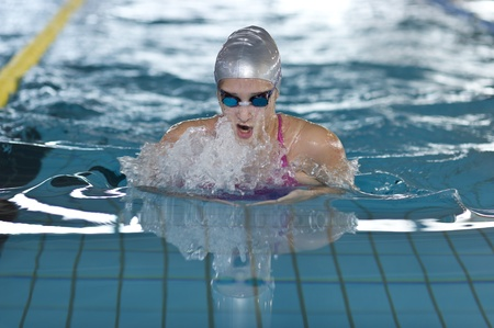 young girl swims breaststroke in the swim pool photo