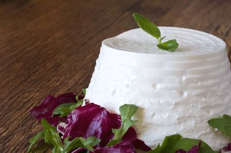 A fresh ricotta with basil leaf on wooden table
