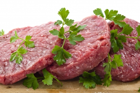 veal sausage: Hamburger of beef on wooden board with parsley Stock Photo