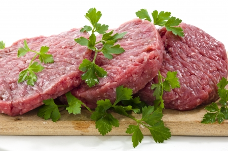 Hamburger of beef on wooden board with parsley photo
