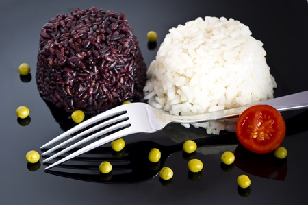 mixed rice with green peas and fork  on black plate