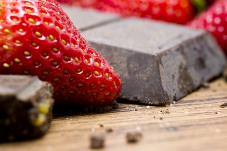 Strawberries  and raw chocolate on wooden table photo