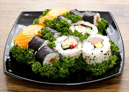 Sushi mixed in black plate on Japan wooden table photo
