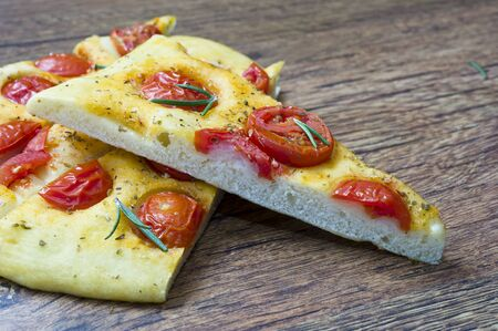 Focaccia with tomato on wooden table photo