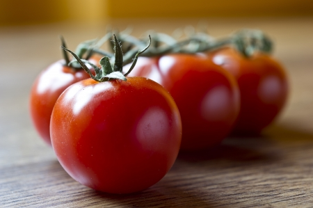 Ripe Fresh Cherry Tomatoes on wooden table photo