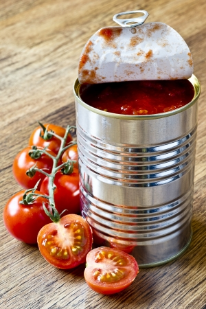 canned raw food and tomatoes on wooden table