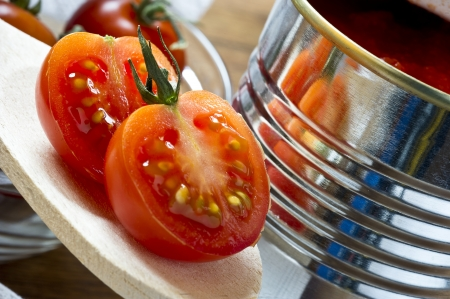 canned tomatoes  and  fresh cherry tomatoes on wooden table