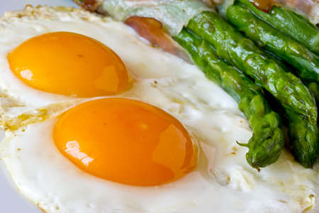 Asparagi with fried egg brown over wooden table photo