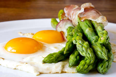 Asparagi with fried egg brown over wooden table Stock Photo