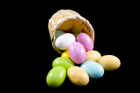 Pastel candy coated Easter chocolates in black background photo