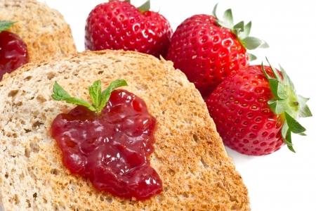 sweet strawberries jam on toast close up on white background photo
