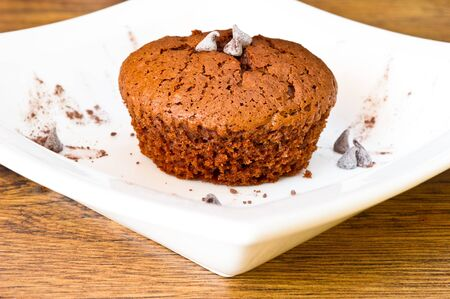 chocolat muffin in white plat on wooden table