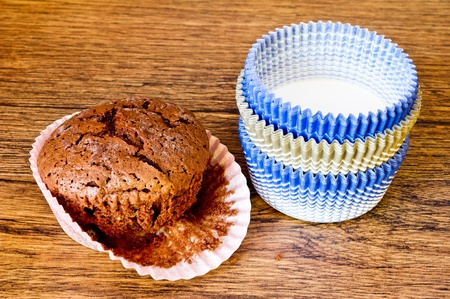 paper molds and chocolat muffin on wooden table Stock Photo - 18731760