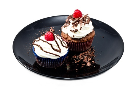 chocolat muffins with   whipped cream and raspberries on black plate photo