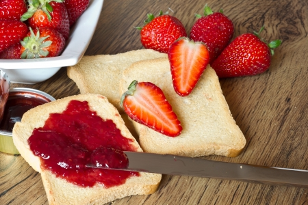 strawberries jam and rusk on wooden table with a knife Stock Photo - 19432426
