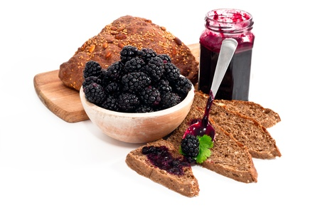 blackberries jam and homemade slices bread on white background photo