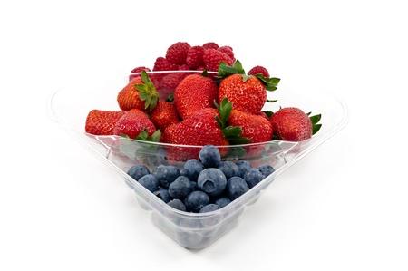 Frutas de la mezcla en el envase de pl�stico de supermercados en el fondo blanco photo