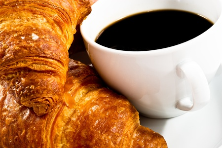 breakfast with cup of black coffee, croissants on white plat - closeup photo