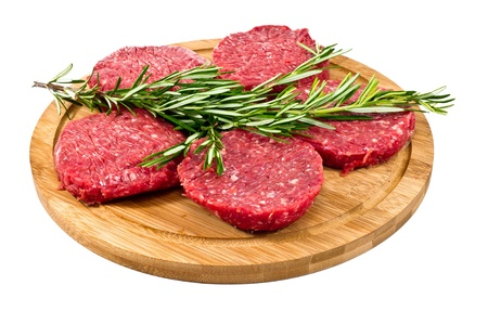 raw hamburgers with cellophane and rosemary on wooden board isolated on white background photo