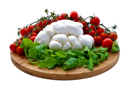 Fresh salad with cherry tomatoes, rucola, mozzarella on wooden board isolated on white background photo