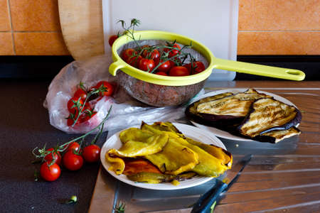 preparing vegetables, peppers and tomatoes  in kitchen board photo