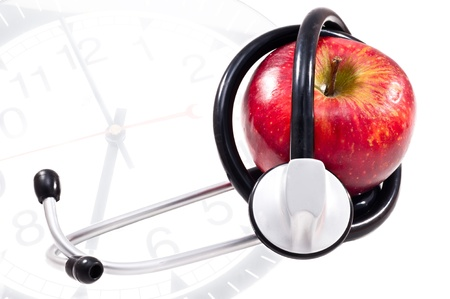 Red Apple and stethoscope on clock  background photo