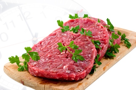 Hamburger of beef on wooden board with parsley on clock photo