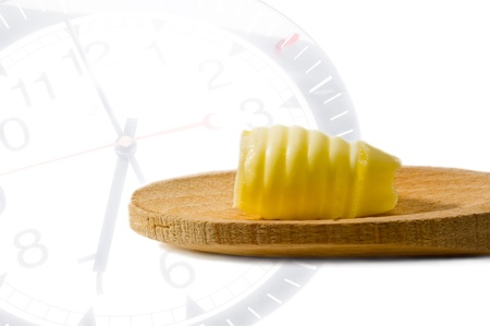 Butter curl on a wooden spoon on clocks  background photo