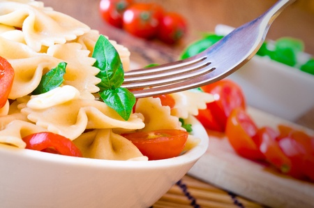 pasta with italian cheese  mozzarella , basil  and red tomatoes photo