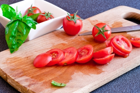 cutting board with tomatoes and basil leaf, knife on background photo