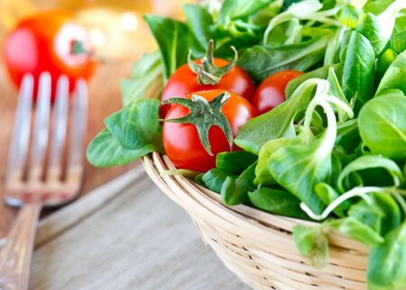 domates: a basket of fresh green salad with tomatoes on wooden table