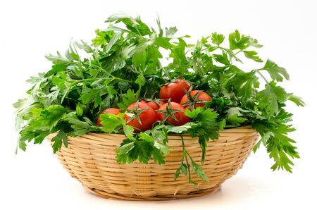a basket of parsley and cherry tomatoes on white background photo
