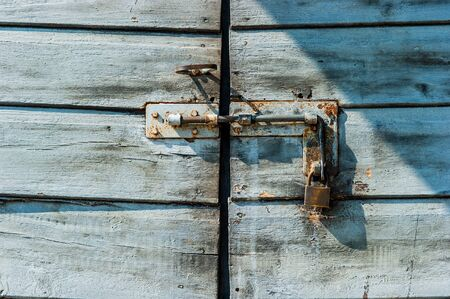 Rusty padlock on an old wooden door  photo