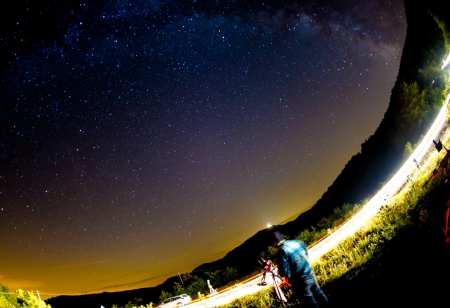 Astronomer working under a night sky  Stock Photo