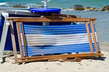 closed beach chairs on  sand with umbrella photo