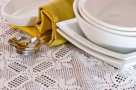 cups and spoons with plates over a white doily photo