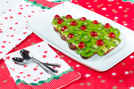 a fruitcake for happy christmas on table wth accessories for dinner photo