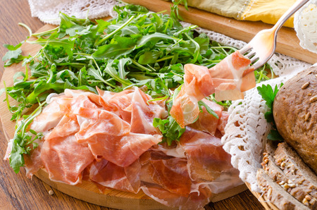 Italian prosciutto crudo ham with green salad called rucola on wooden board photo