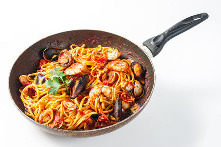 Spaghetti with mussels and tomato sauce on white background photo