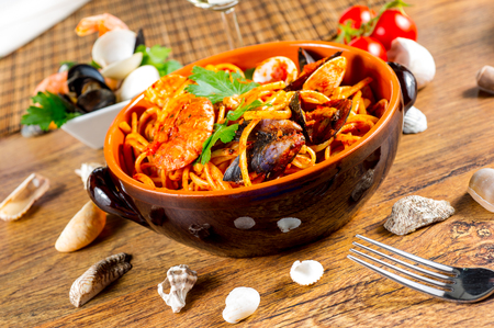 Spaghetti with mussels and tomato sauce on wooden table photo
