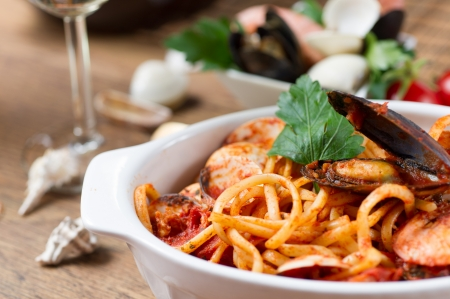 Spaghetti with mussels and tomato sauce on wooden table